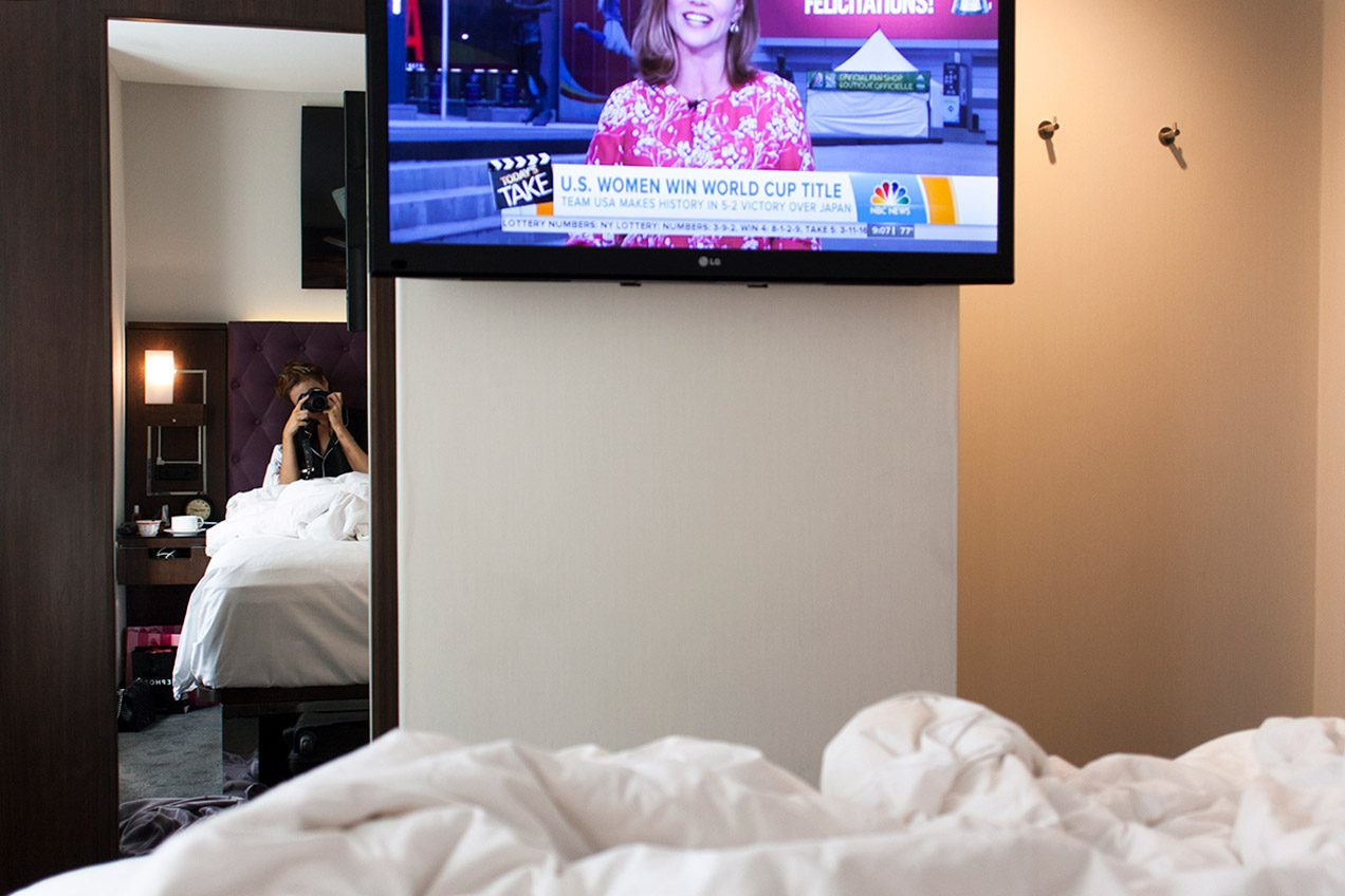 Girl in pajamas taking a self-portrait from her hotel bed