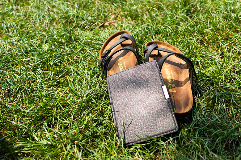 Birkenstock sandals and a Kindle on grass