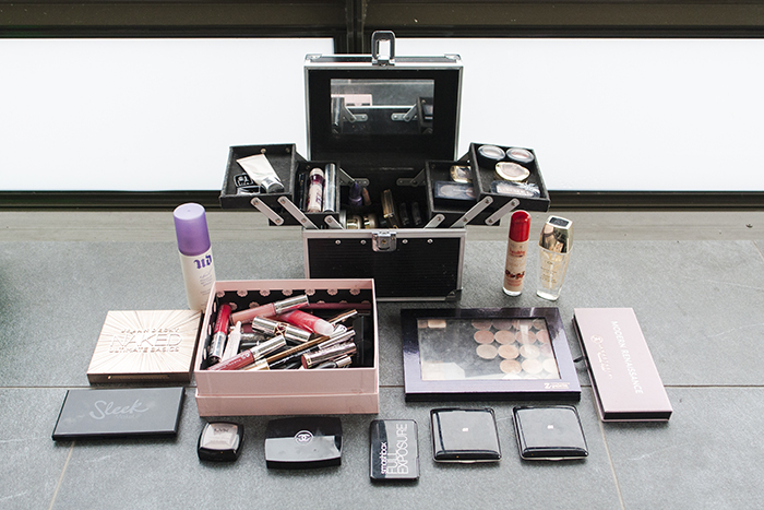 Makeup case full of makeup, next to even more makeup placed in front of it