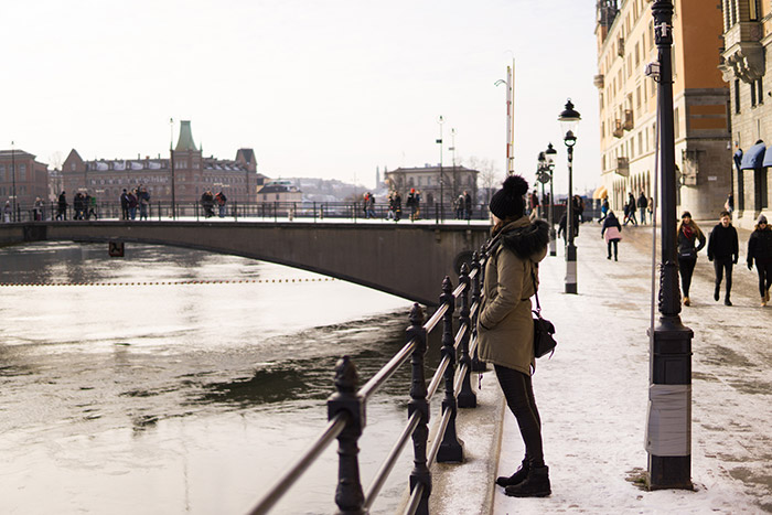 Maja standing on a snowy street, looking at the river and bridge to Stockholm Royal Castle