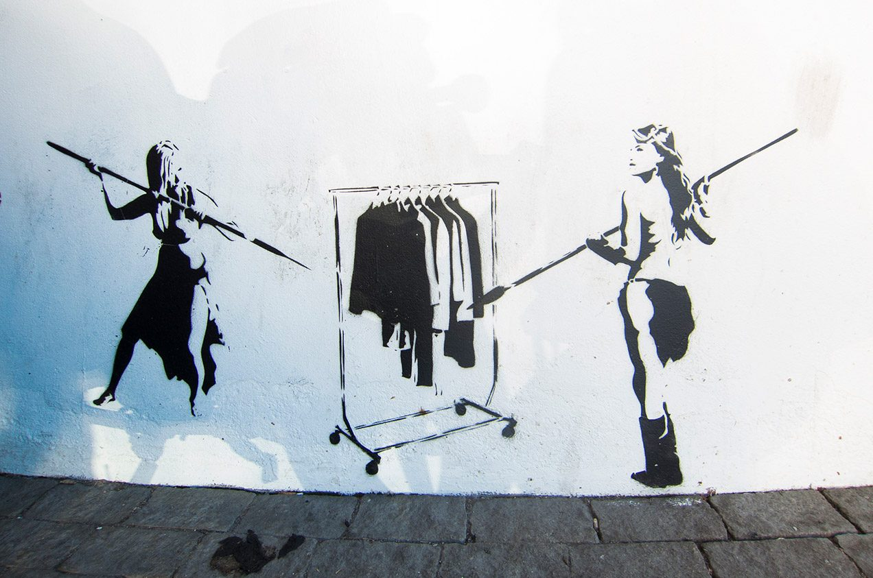 Graffiti of two cavewomen with spears hunting a clothes rack