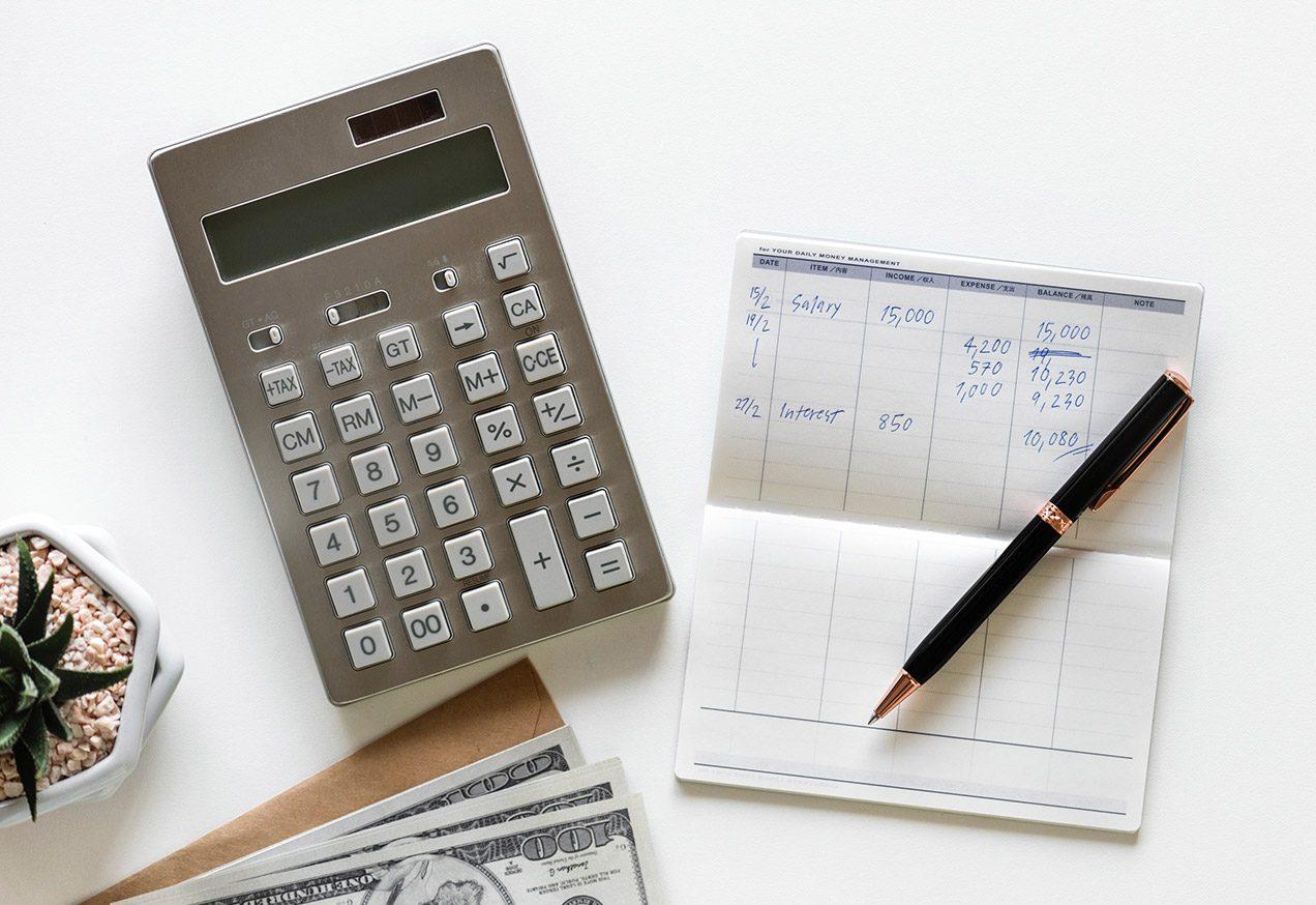 Photo of calculator, a simple handwritten budget, and dollar bills